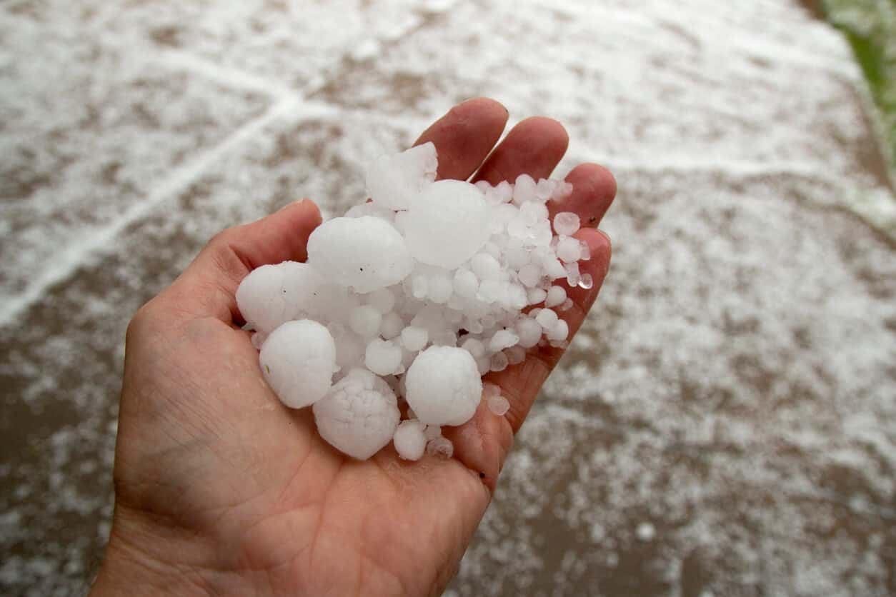 Hail in hand of storm restoration experts Dolan Roofing.