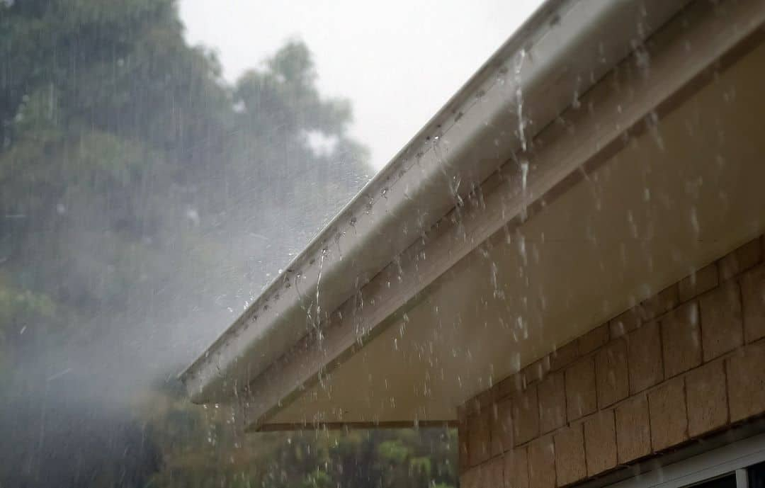 a roof and gutters in heavy rain