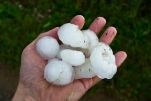 a hand holding large hail stones
