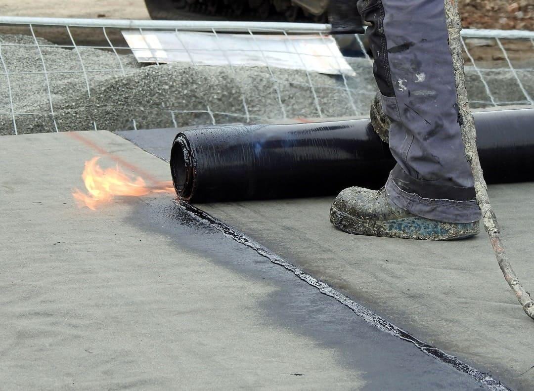 a roofer installs modified bitumen roofing