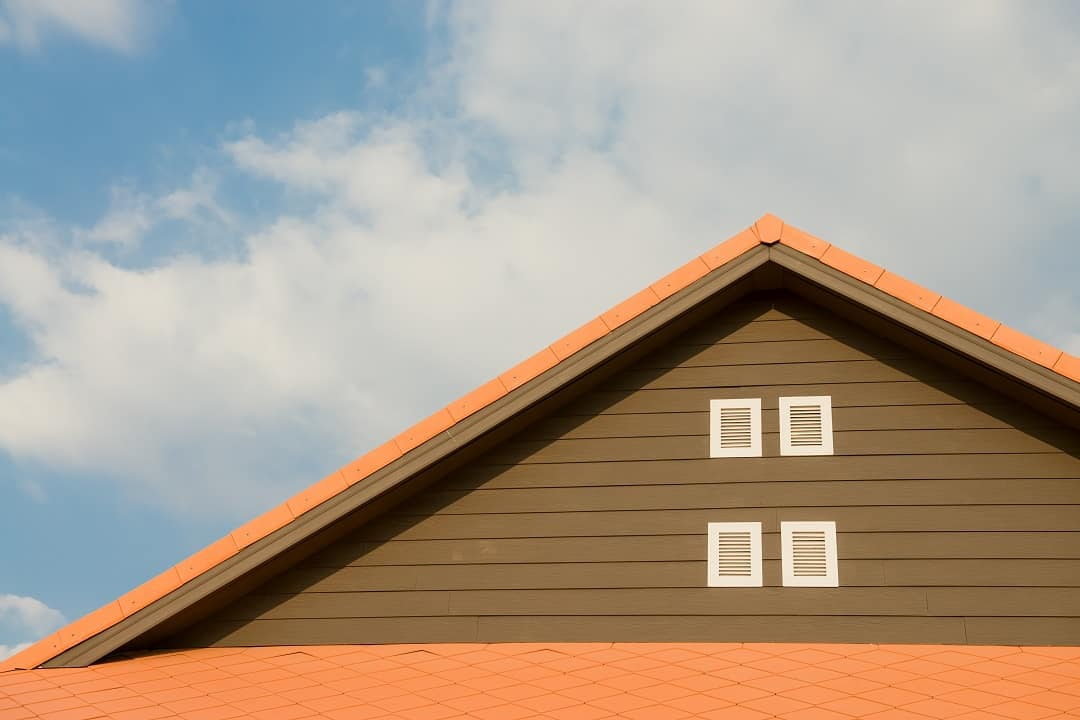 an orange roof with clouds in the background